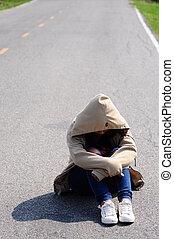 Sad woman hug her knee on the road