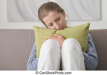 Sad woman hugging a pillow