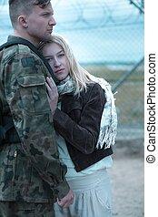 Sad woman hugging military husband and saying goodbye