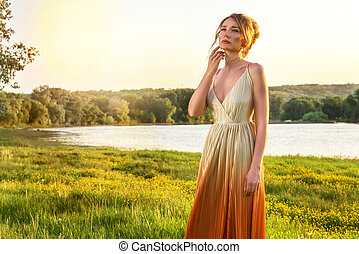 Sad Woman in a long glamorous dress at sunset. Girl lovely look sadness eyes. Beautiful landscape views