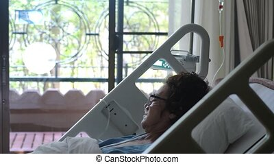 Sad woman in aged wearing eyeglasses lies in a hospital bed...