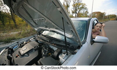 Sad woman in broken car - Road trip car trouble. A young...