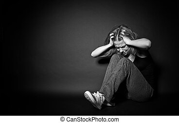 sad woman in depression and despair crying clutching his hands behind his head on black dark background