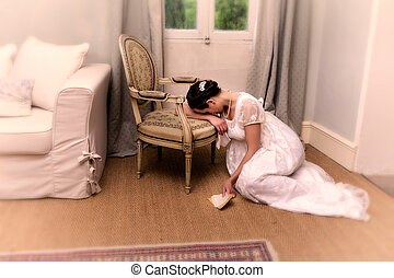 Depressend youg woman in authentic regency dress holding a letter and leaning against an antique chair