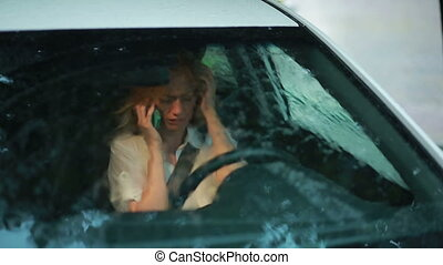 sad woman is on the phone. girl crying in the car. rain on the street