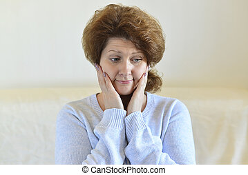 Sad woman looking away at home in living room