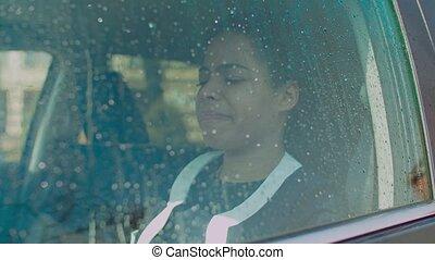 Sad woman looking through car window with raindrops