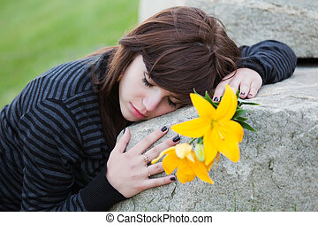 Sad woman lying on the tombstone
