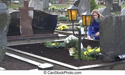 Sad woman put candle on grave of loved father brother in cemetery. 4K