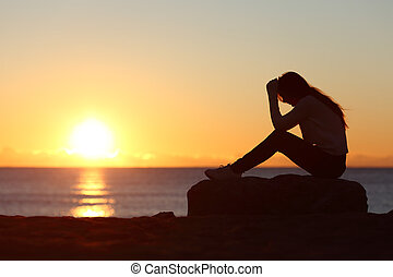 Sad woman silhouette worried on the beach at sunset with the...