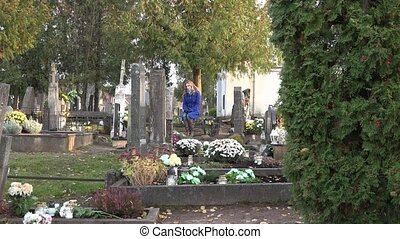 Sad woman sit on bench near grave of husband father in cemetery. Zoom out. 4K
