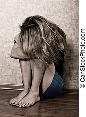 Sad woman sitting alone in a empty room next to the bed. domestic violence