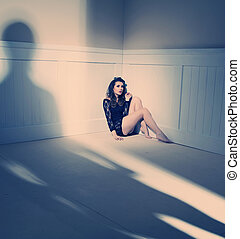 Sad woman sitting alone in a empty room - Sad brunette woman...