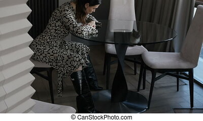 Sad woman sitting at table - Attractive sad woman sitting at...