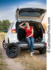 Sad woman sitting in open trunk of broken car on the road
