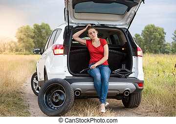 Sad woman sitting in open trunk of broken car on the rural road
