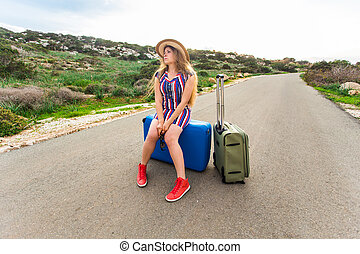 Sad woman sitting on suitcase