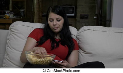 Sad woman sitting on the couch and eating popcorn