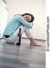 Sad woman sitting on the floor hugging her knees with a bottle of red wine crying, divorce concept, parting, alcoholism