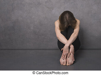 Sad woman, studio shot - Sad woman sitting on a floor near...
