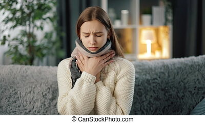 Sad young woman in warm sweater and scarf sitting suffering from sore throat while staying at home. Concept of sick and tired.