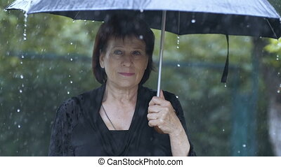 Sad Woman under umbrella - Sad woman under umbrella at heavy...