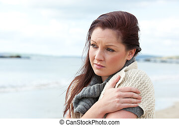 Sad woman warming herself standing on the beach
