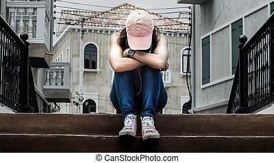 sad woman wearing a hat and hugging knees on stair, dark tone.