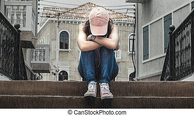 sad woman wearing a hat and hugging knees on stair in the rain