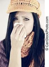 Sad woman with flu sneezing isolated
