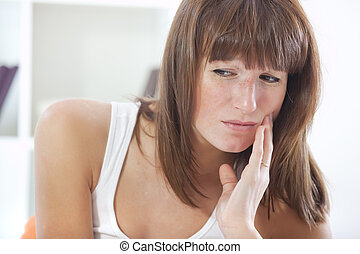 woman with toothache - sad woman with toothache sitting in...