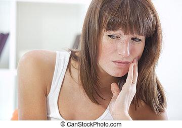 woman with toothache - sad woman with toothache sitting in ...