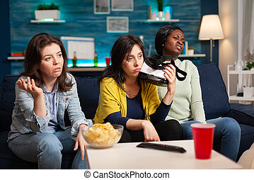 Sad women after losing virtual reality gaming competiton holding vr headset sittingon couch. Mixed race group of people hanging out together having fun late at night in living room