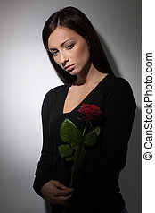 Sad women. Young depressed women holding a rose and looking away