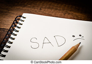SAD word on diary book with wooden pencil.