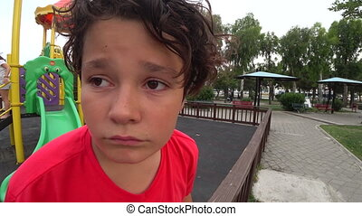 Sad young boy at the playground