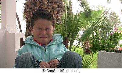 Sad young boy crying