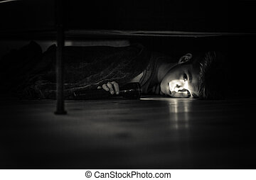 Sad Young Boy with Flashlight Lying Under his Bed