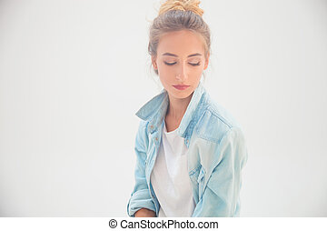 sad young casual woman looking down