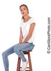 sad young casual woman sitting on chair