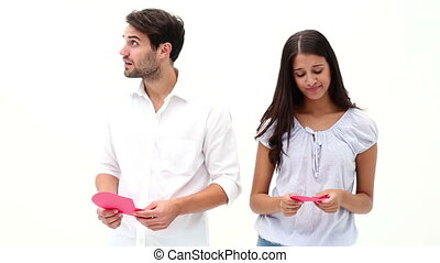 Sad young couple holding two halves of broken heart on white...