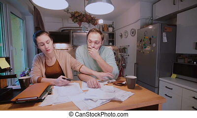 Sad young couple paying the bills. Man and woman sitting in...
