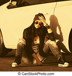 Sad young fashion hipster woman sitting next to her car