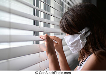 Sad young girl forced to stay at home as the pandemic coronavirus looking out of home window. Real people. Copy space