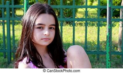 Sad young girl on swing