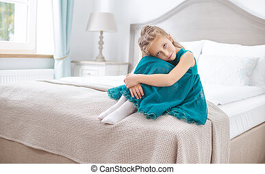 Sad young girl sitting in bedroom