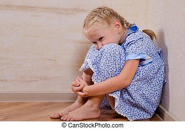 Sad young girl sitting in corner