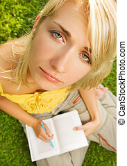 Sad young girl sitting oudoors on a grass and reading book