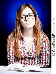 Sad young girl with nerd glasses and open exercise book