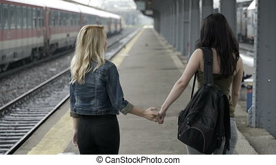 Sad young girls walking hand in hand in train station hugging  before separation